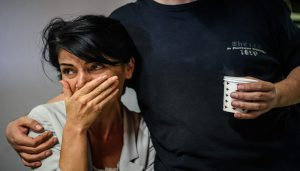 An employee of prominent pro-Kurdish television channel IMC TV cries as Turkish police raided the headquarters of the TV channel on October 4, 2016 in Istanbul. / AFP PHOTO / OZAN KOSE