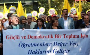 """People hold a banner reading """"Give the teachers the rights for a strong and democratic society"""" asd they take part in a demonstration of Turkish teachers outside the Turkish Education Ministry in Ankara, on October 5, 2016 to protest against the government's education policies and to call for secularism in education. / AFP PHOTO / ADEM ALTAN"""