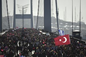 People walk on the July 15 Martyrs' Bridge, known as the Bosphorus Bridge, during the 38th annual Istanbul Marathon on November 13, 2016. / AFP PHOTO / YASIN AKGUL