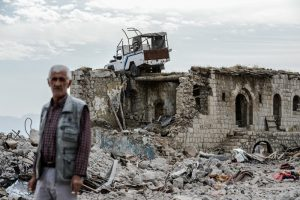 A man stands near a damaged building upon his arrival in Sirnak city on November 14, 2016  after a 246-day curfew was partially lifted. / AFP PHOTO / ILYAS AKENGIN