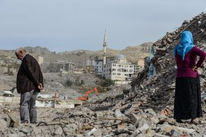 People stand amidst the rubble in Sirnak city on November 14, 2016, after a 246-day curfew was partially lifted. / AFP PHOTO / ILYAS AKENGIN