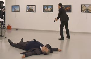 """This picture taken on December 19, 2016 shows Andrey Karlov (L), the Russian ambassador to Ankara, lying on the floor after being shot by a gunman (R) during an attack during a public event in Ankara. A gunman crying """"Aleppo"""" and """"revenge"""" shot Karlov while he was visiting an art exhibition in Ankara on December 19, witnesses and media reports said. The Turkish state-run Anadolu news agency said the gunman had been """"neutralised"""" in a police operation, without giving further details. / AFP PHOTO / STRINGER"""