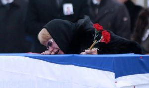 Marina Davydova Karlova, widow of late Russian Ambassador to Turkey Andrei Karlov, reacts in front of his coffin, during a ceremonial farewell with full state honours on the tarmac of Ankara's Esenboğa Airport on December 20, 2016. / AFP PHOTO / ADEM ALTAN