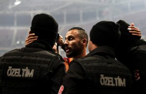 Galatasaray player Yasin Oztekin (C) hugs Turkish policemen after scoring a goal on December 11, 2016, a day after twin attacks near the home stadium of Besiktas football club. Turkey declared a day of national mourning after twin bombings targeting police struck the heart of Istanbul near the home stadium of football giants Besiktas, killing 38 people. / AFP PHOTO / STR