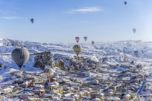 NEVSEHIR, TURKEY - JANUARY 06: Hot air balloons fly over snow covered Cappadocia, a historical region in Central Anatolia, largely in Nevsehir Province, known for the fairy chimneys, during the winter season on January 06, 2017 in Nevsehir, Turkey. Sercan Kucuksahin / Anadolu Agency