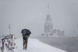 A man walks in a snow covered sidewalk near the Bosphorus during the heavy snowfall in Istanbul, Turkey on January 07, 2017. Arif Hudaverdi Yaman / Anadolu Agency