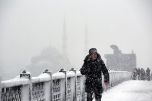 A man walks on snow covered Galata Bridge over the Golden Horn during the heavy snowfall in Istanbul, Turkey on January 07, 2017. Erhan Sevenler / Anadolu Agency