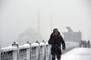 A man walks on snow covered Galata Bridge over the Golden Horn during the heavy snowfall in Istanbul, Turkey on January 07, 2017. Erhan Sevenler / Anadolu Agency