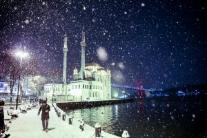 People are seen around the Ortakoy mosque in snow covered street during the heavy snowfall in Istanbul's Ortakoy district, Turkey on January 07, 2017. Berk Ozkan / Anadolu Agency