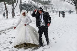 A newly married couple walk at Sultanahmet square during snowfalls in Istanbul on January 8, 2017. / AFP PHOTO / YASIN AKGUL