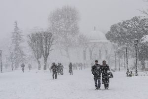 People walk at Sultanahmet square during snowfalls in Istanbul on January 8, 2017. / AFP PHOTO / YASIN AKGUL