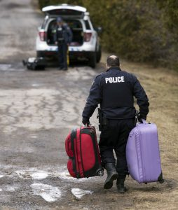 A member of the RCMP carries luggage belonging to a couple who claimed to be from Turkey after they crossed the US/Canada border and were arrested February 27, 2017, in Champlain, New York. There continues to be an increasing number of people crossing the US border into Canada illegally. / AFP PHOTO / Don EMMERT