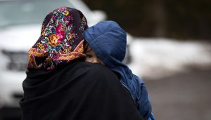 HEMMINGFORD, QUEBEC - FEBRUARY 23: A mother and child from Turkey wait to be put into a police vehicle by the Royal Canadian Mounted Police after they crossed the U.S.-Canada border into Canada, February 23, 2017 in Hemmingford, Quebec. In the past month, hundreds of people have crossed Quebec land border crossings in attempts to seek asylum and claim refugee status in Canada. Drew Angerer/Getty Images/AFP