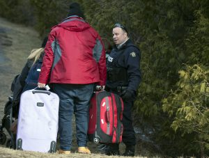 A man who claimed to be from Turkey is questioned by the RCMP after crossing the US/Canada border February 27, 2017, in Champlain, New York. There continues to be an increasing number of people crossing the US border into Canada illegally. / AFP PHOTO / Don EMMERT